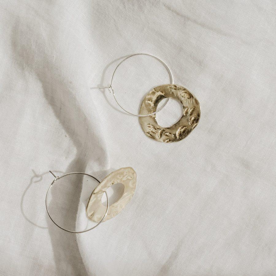 Ochre ceramics jewellery around the sun hoops On fabric